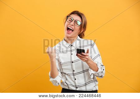 Portrait of delighted woman in plaid shirt and eyeglasses clenching fist like winner while using mobile phone isolated over yellow background