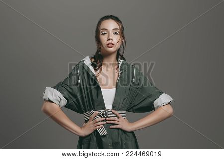 young fashionable girl posing in autumn raincoat, isolated on grey