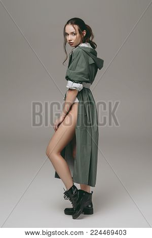 beautiful young stylish girl posing in raincoat, isolated on grey