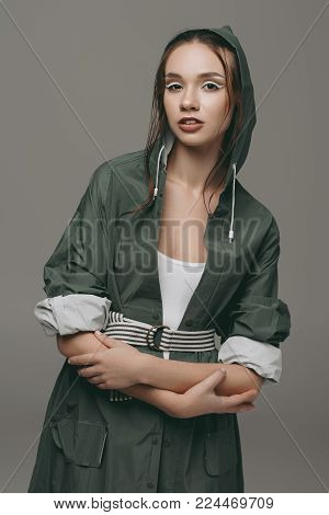 beautiful young girl posing in raincoat, isolated on grey