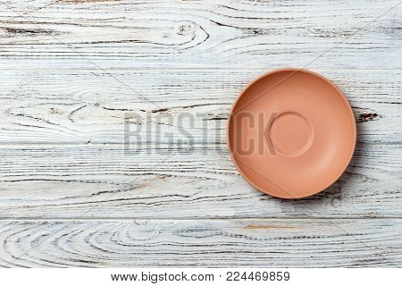 Orange round plate top view on a background of old wood table plank. matte round plate.