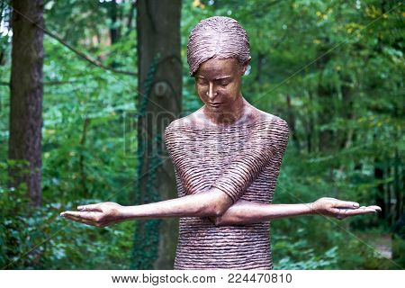 DRESDEN, GERMANY - SEPTEMBER 8, 2017: A statue of the Grieving Girl in the cemetery Heidefriedhof. The sculpture depicts a girl in a simple dress, her arms crossed over her chest so that the whole figure forms a cross.