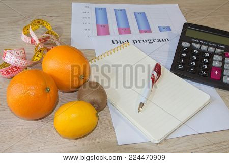 Healthy natural organic food diet, ripe harvest. Fruit composition, measuring tape, calculator with diet plan. Low-fat diet