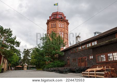 Stockholm, Sweden - August 11, 2014- Traditional old house and Bredablick tower dated 1874 at Skansen, the first open-air museum and zoo, located on the island Djurgarden.