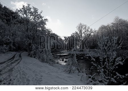 The white and black view on river under snow