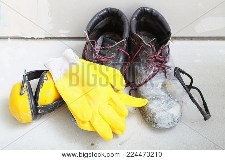 Renovation at home. Construction equipment tools work boots yellow protective noise muffs gloves glasses in building site.