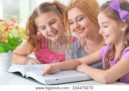 Portrait of mother with daughters reading book