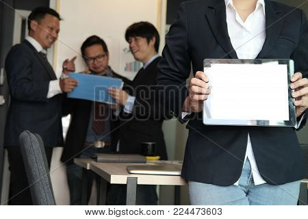 Businesswoman Hold Tablet At Workplace. Young Woman Shows Information In Touchpad At Office. Freelan