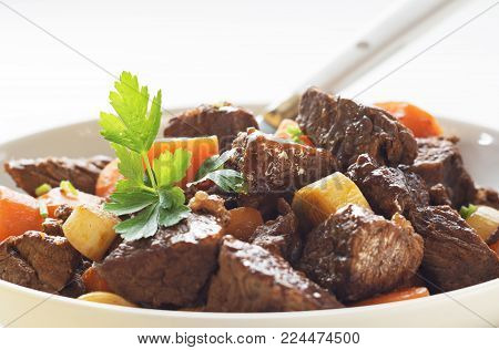 Beef meat stewed with carrots  in white plate.