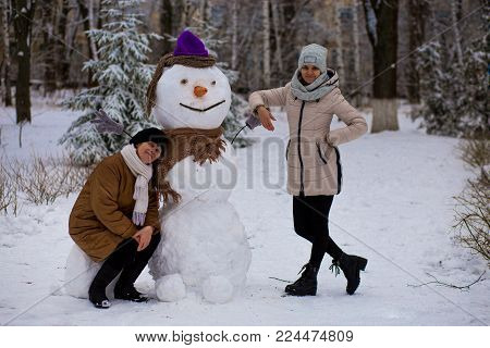 Mother and adult daughter sculpt a big real snowman, Happy family in winter park
