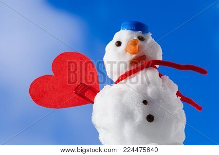Little happy christmas snowman in blue screw top as hat red scarf and with clip red heart love symbol outdoor. Winter season seasonal specific valentine's day. Blue sky background.