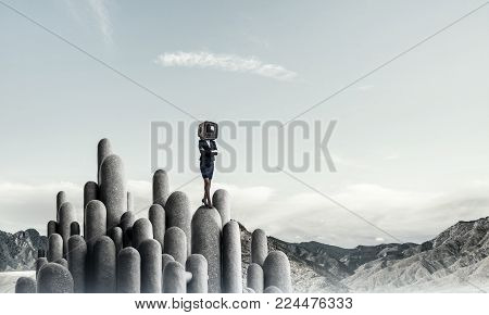 Business woman in suit with an old TV instead of head keeping arms crossed while standing on the top of stone columns with beautiful landscape on background.