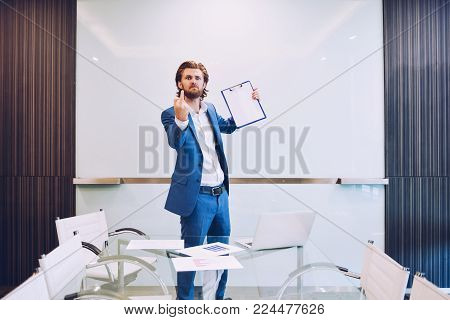 Angry business man showing the middle finger in meeting room
