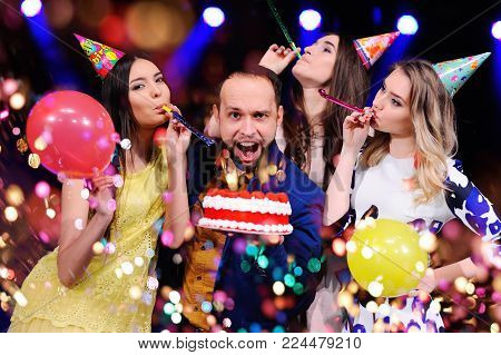 a guy and three girls rejoice and celebrate the party in the night club. Birthday, new year, corporate party, best friends