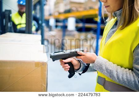 Unrecognizable warehouse woman worker or supervisor with barcode scanner. A mobile handheld PC with barcode scanner.