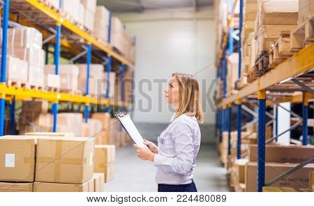 Young woman warehouse worker or supervisor with clipboard, controlling stock.