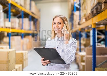Young woman warehouse worker or supervisor with smartphone, making a phone call.