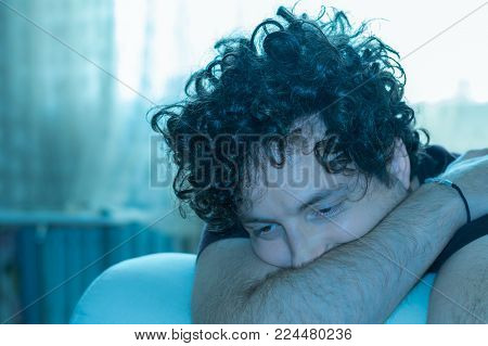 Young Handsome Man With Curly Hair Sleeping On The Couch
