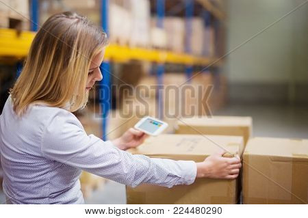 Young woman warehouse worker or supervisor with smartphone.