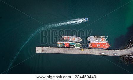 Aerial views over Gansbaai harbor in the overberg in the Western Cape of South Africa With fishing vessels laying at anchor in the harbor