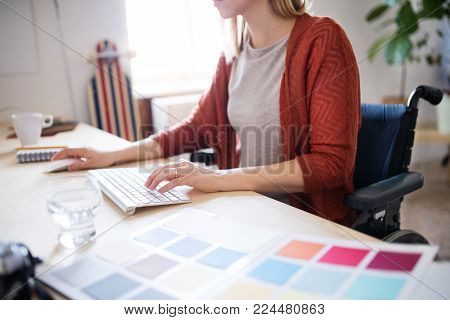 Unrecognizable businesswoman in wheelchair sitting at the desk, working.
