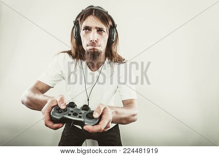 Lifestyle of young people. Student man spending time on playing games videogames console playstation. Long haired guy focus on gaming.