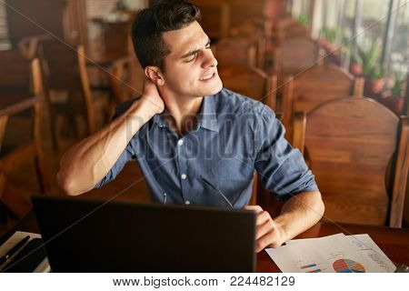 Businessman with backpain after long hours at work rubbing his neck because of ache. Overworked handsome freelancer man with scoliosis working with laptop. Health problems concept.
