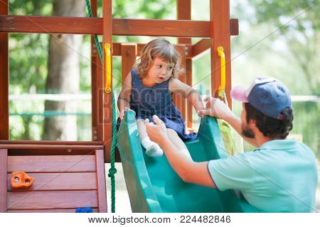 Little Girl Playing With Her Father On A Playground.