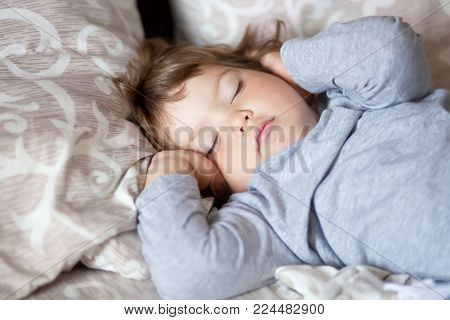 Adorable Little Girl Sleeping In The Bed.