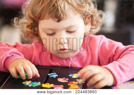 Adorable Happy Little Child Playing With Puzzle.
