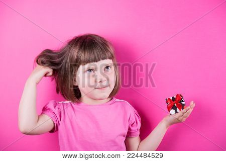 Funny Smiling Little Girl Holding Pretty Spotted Gift Box In Her Hands On Bright Pink Background