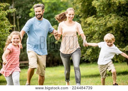 Happy family with two children and parents in the nature