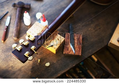 Acoustic Guitar on or steel string guitar repair desk with on e tuner or tuning peg detached. Shallow depth of field.