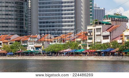 BOAT QUAY, SINGAPORE - AUGUST 18, 2009: Traditional shophouses at Boat Quay, a historical quay in Singapore, situated upstream from the mouth of the Singapore River on its southern bank. The city's financial district is situated in the background.