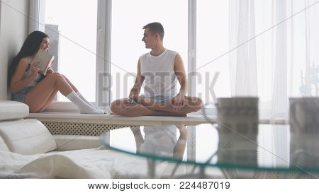 Young happy couple sitting on the windowsill, girl reading a book and laughing, the guy tickles her, relationship between people poster