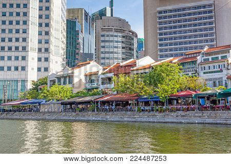 BOAT QUAY, SINGAPORE - AUGUST 17, 2009: Traditional shophouses at Boat Quay, a historical quay in Singapore, situated upstream from the mouth of the Singapore River on its southern bank. The city's financial district is situated in the background.