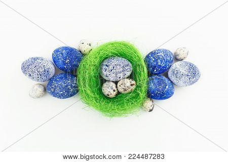Blue speckled easter eggs and quail eggs in nest isolated on white background. Flat lay, top view. Happy Easter.