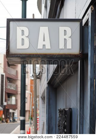 Generic inner city vibe BAR sign. Bar sign with lots of inner city grunge vibe and character, white lettering, grey wall background and a little bit of rust flavor.