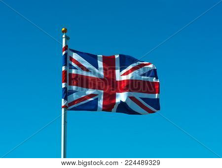 A Union Flag Flying On Flagpole With Blue Sky