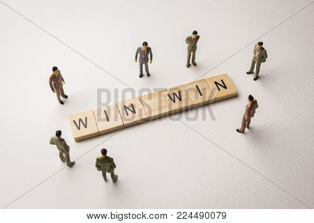 Miniature figures businessman : meeting on win win letters by wooden block word on white paper background, in concept of business and corporation