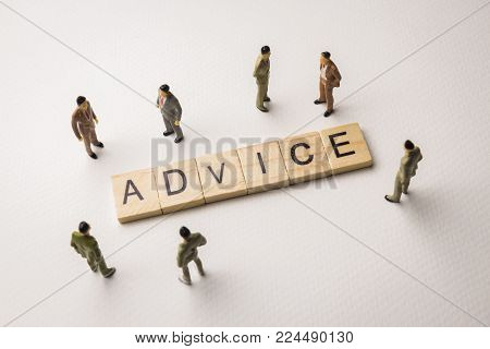 Miniature figures businessman : meeting on advice letters by wooden block word on white paper background, in concept of business and corporation