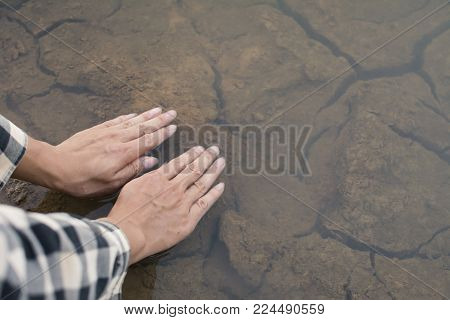 Close up hands of Asian man on nature ,crisis of water drought concept, selective and soft focus
