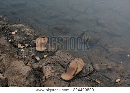 Sandals on nature ,crisis of water drought concept, selective and soft focus