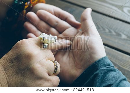 Palmistry fortune teller reads lines on man hand or palm to tell his future, top view, selective focus, toned