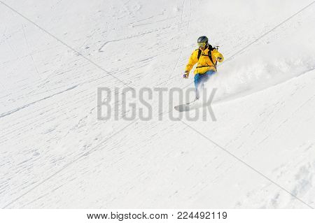 A man a snowboarder freerider descends the backcountry at high speed from a slope leaving behind a trail of snow powder. The concept of freeride culture and backcountry destinations in snowboarding