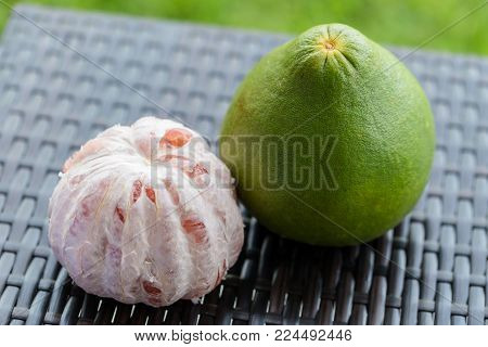 Pomelo on brown plastic rattan weave table. Close up.