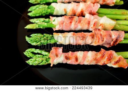 Green asparagus wrapped into smoked bacon on a black plate