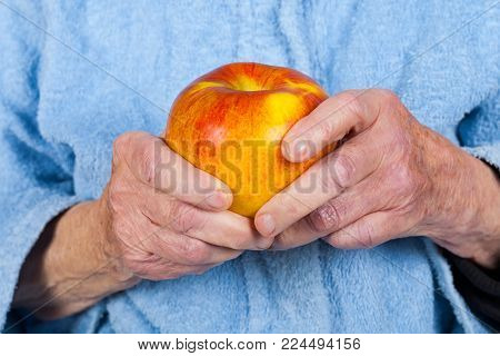 Old Lady's Hands Holding An Apple