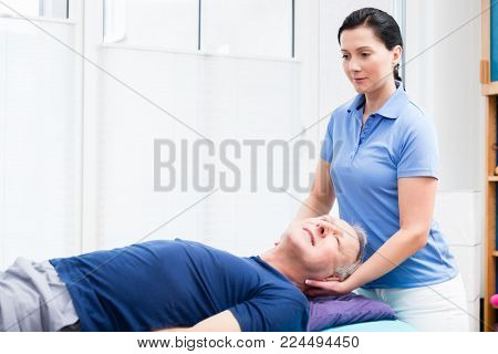Elderly man getting massage from physio