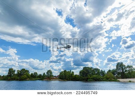 White helicopter over water against the sky and trees.